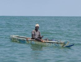 Fisherman with a line on a small boat Gambia by slingeraar