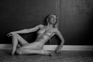 Nude woman against the wall by guns
