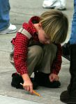 Little Boy Drawing on Ground by Della-Stock