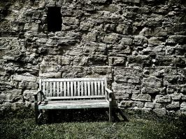 Wooden bench in front of a stone wall by mgot