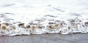 Waves on sand by lucyparryphotography