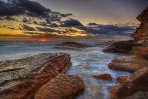 Sunrise on a rocky coast by Kounelli1